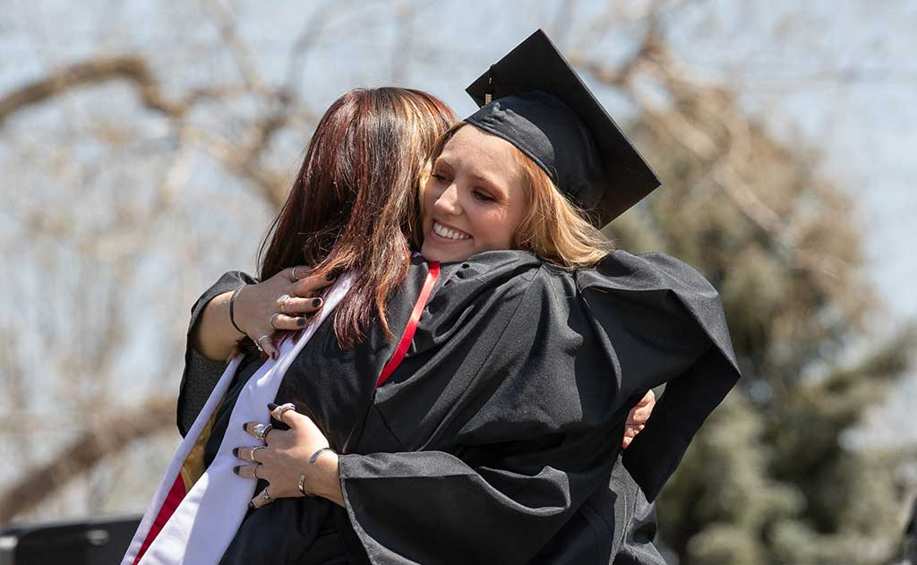 RMCAD graduate hugging faculty on graduation day