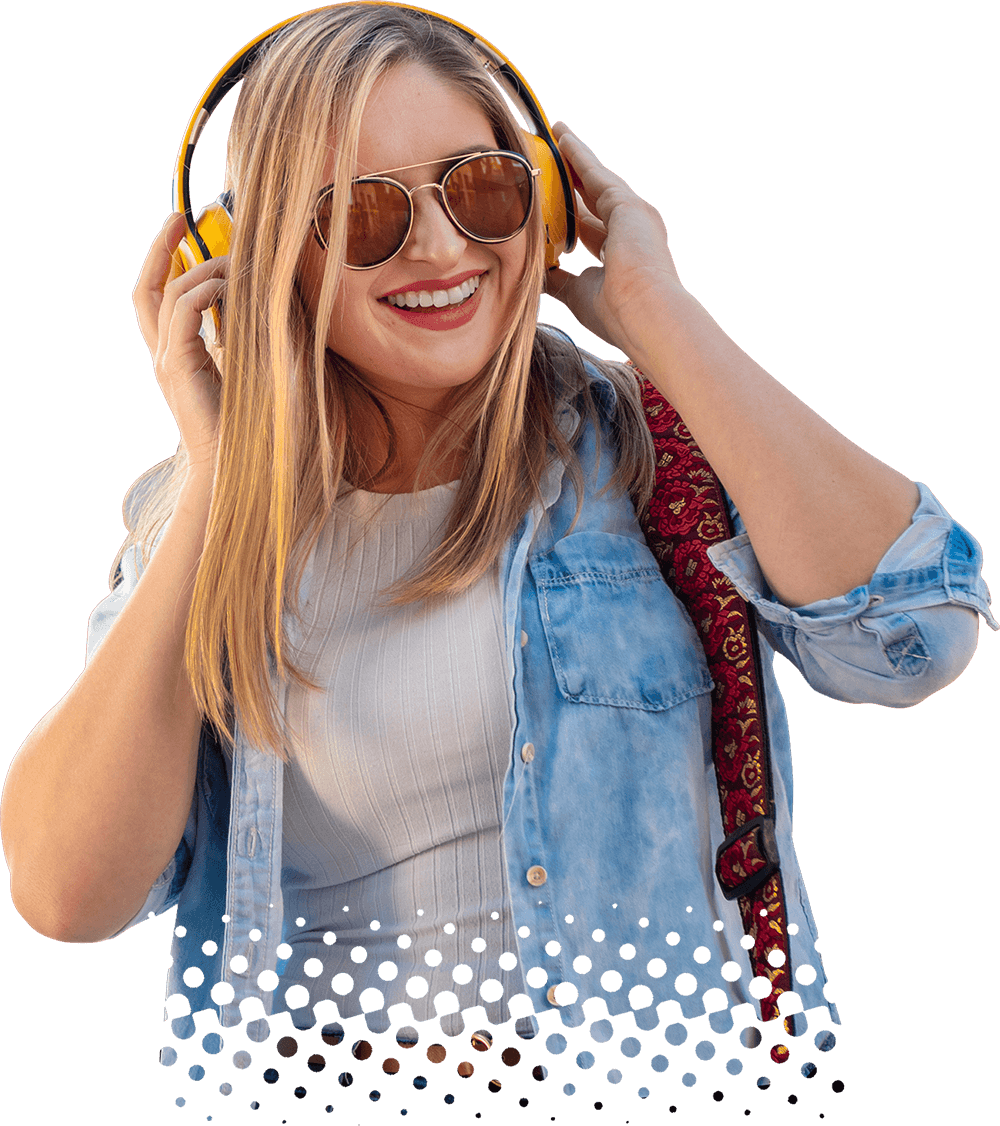 Female music production student smiling and wearing headphones